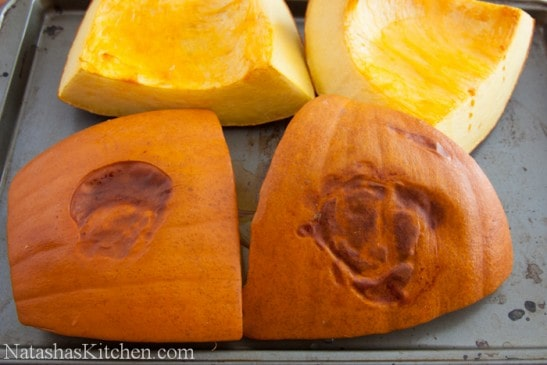 A baking pan with four pieces of cooked pumpkin