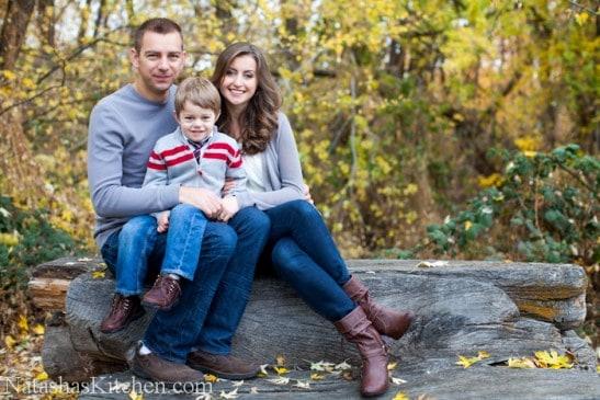 Natasha and her husband sitting on a tree log with their son sitting on her husband\'s lap