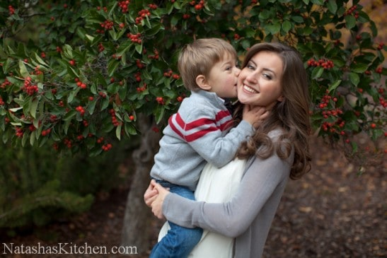 Natasha holding here son with him kissing her cheek