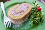 A slice of biskvit raspberry roulade  on a green plate