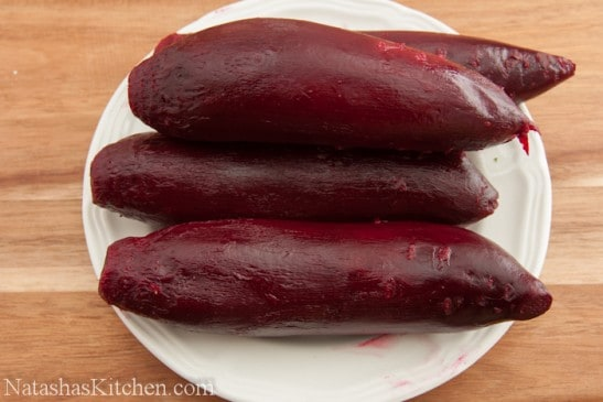 Four large, cooked beets on a plate
