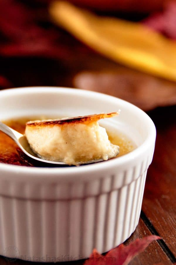 A pumpkin creme brûlée with a scoop being taken out with a spoon
