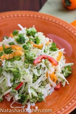An orange plate with cabbage and bell pepper salad