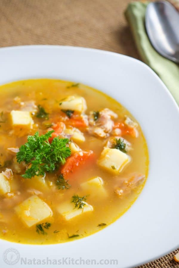 A white bowl of Mom\'s split pea soup garnished parsley