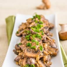 A long plate of mushrooms in a sour cream sauce garnished with green onions