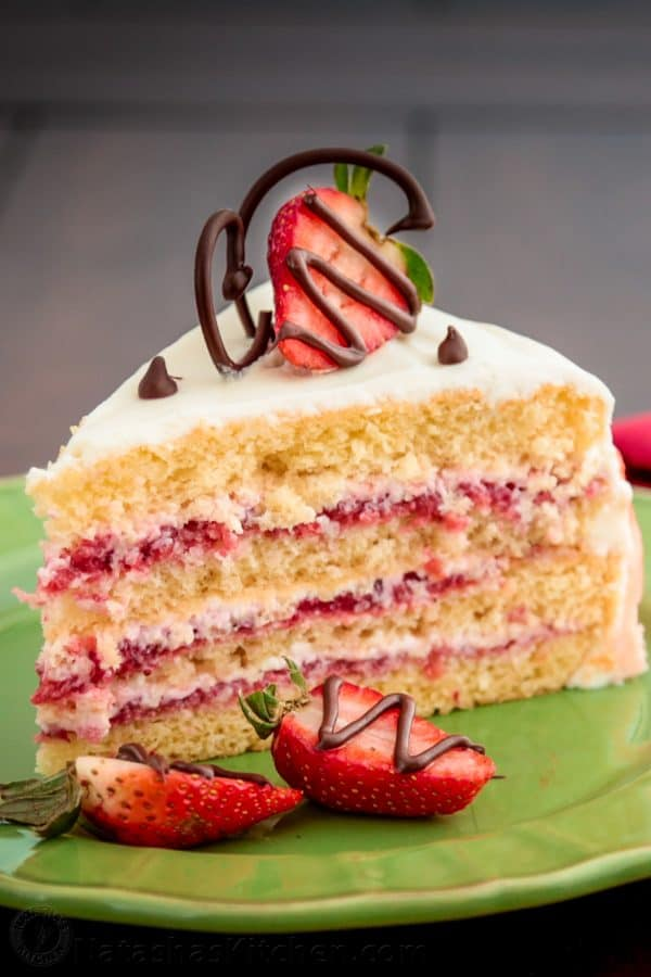 A slice of strawberry layer cake with halved strawberries on top and beside it