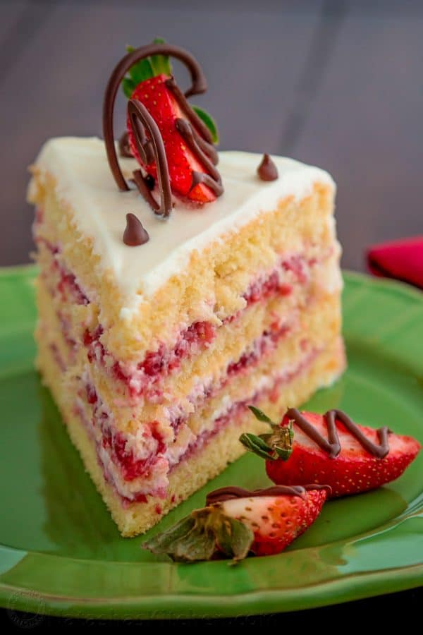 A close up of a slice of a strawberry layer cake