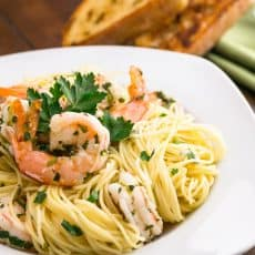 A plate of angel hair with lemon shrimp scampi with two toasted baguette slices behind the plate