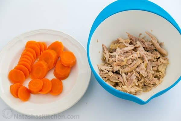 A plate with sliced carrots and a bowl of shredded chicken