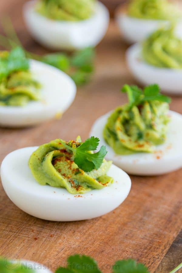 A close up of guacamole stuffed eggs on a cutting board