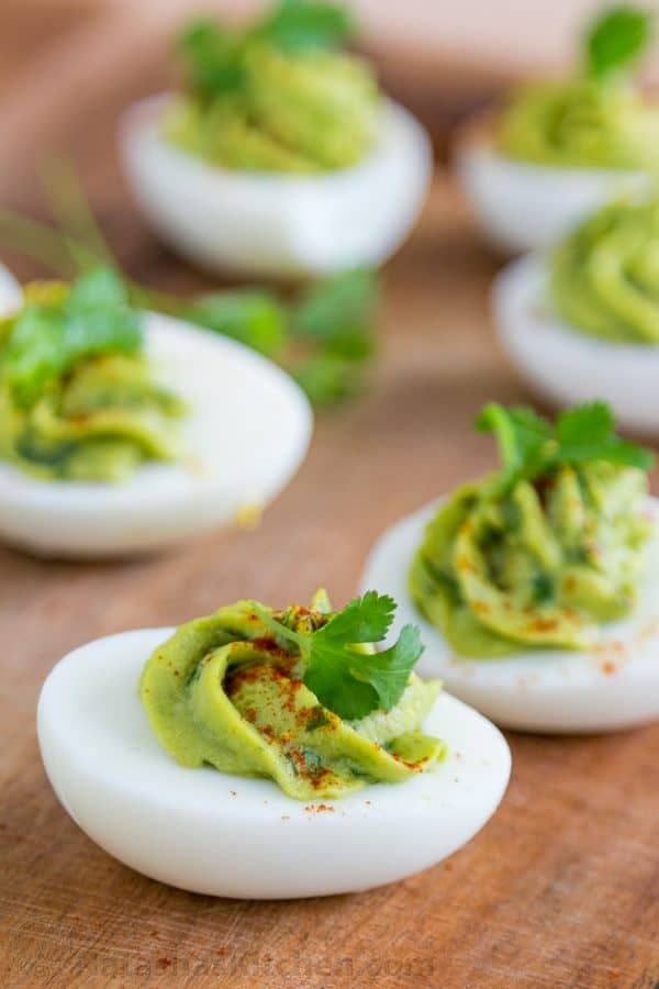Guacamole Stuffed Eggs on a wooden board garnished with cilantro and paprika