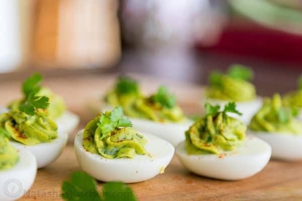 A cutting board with guacamole stuffed eggs