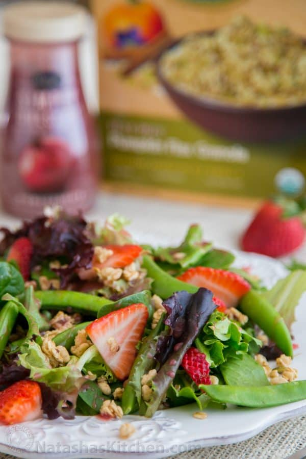 A plate of strawberry, snap pea and mixed green salad