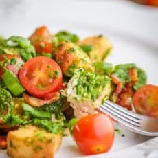 A plate and fork placed into creamy spinach salad with chicken and baby tomatoes