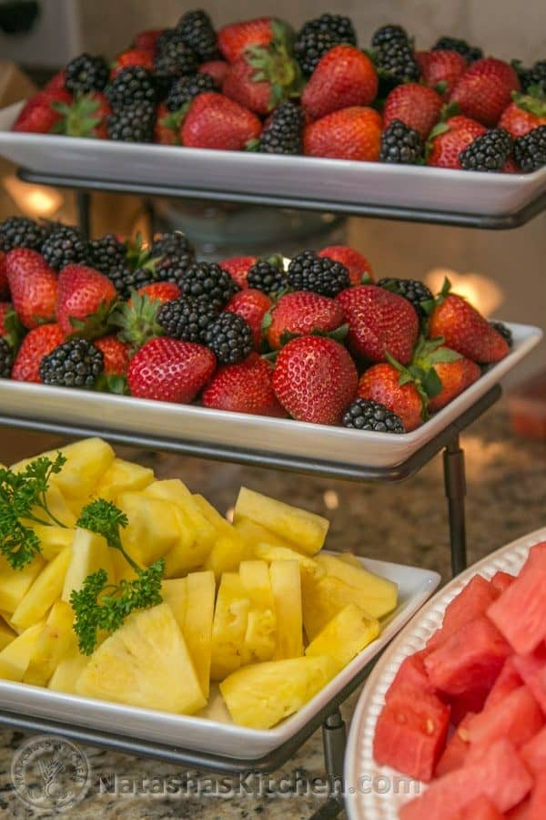 A three-tier tray with fruits such as pineapple, strawberries, and blackberries on it
