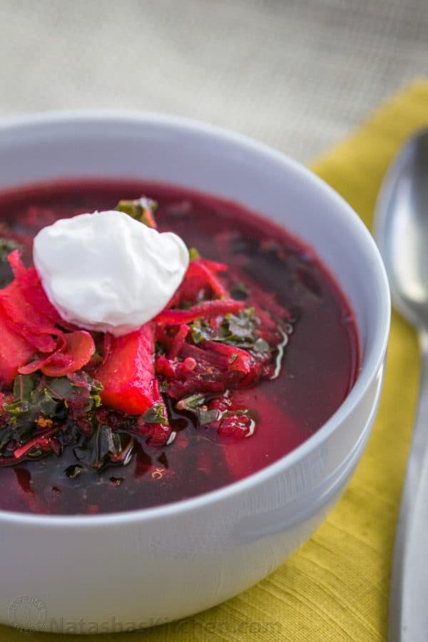A bowl of red borsch garnished with sour cream with a spoon beside it