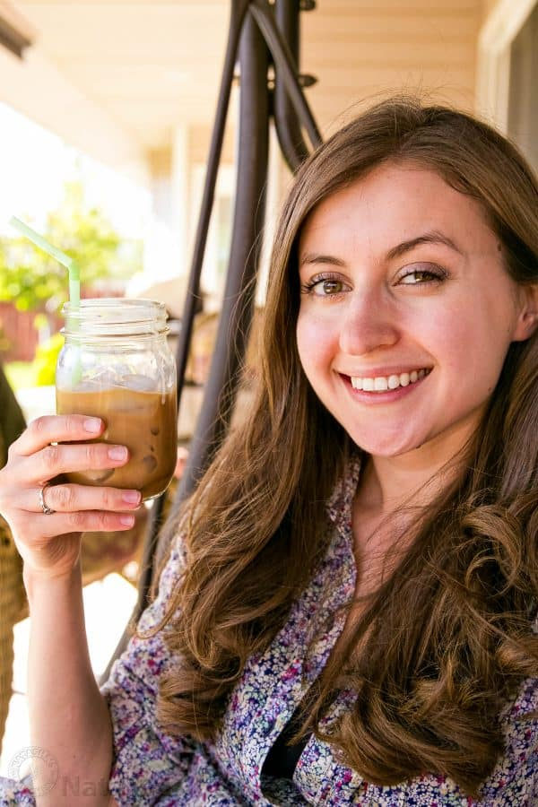 Natasha holding an iced coffee with condensed milk in a mason jar with a straw