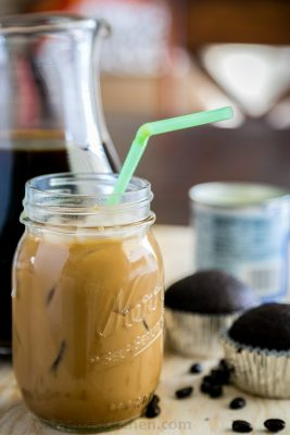 Iced coffee with condensed milk in a mason jar with a straw and cupcakes in the background