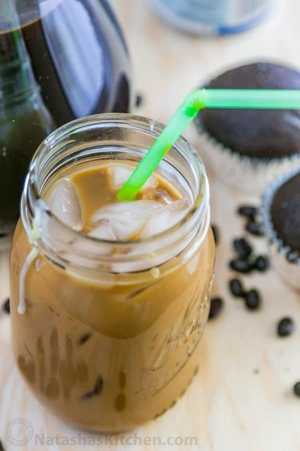A close up of an iced coffee with condensed milk with cupcakes, coffee and coffee beans around the jar
