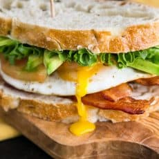 A close up of a breakfast BLT sandwich on a cutting board