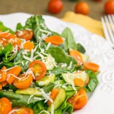 A plate of spinach salad with tomatoes and cucumbers in the background and a fork beside the plate