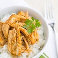A bowl of rice topped with sweet and spicy baked chicken and garnished with parsley