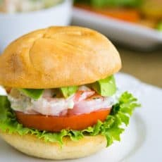 A close up shrimp sandwich on a white plate