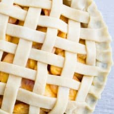 A raw peach pie with a lattice crust