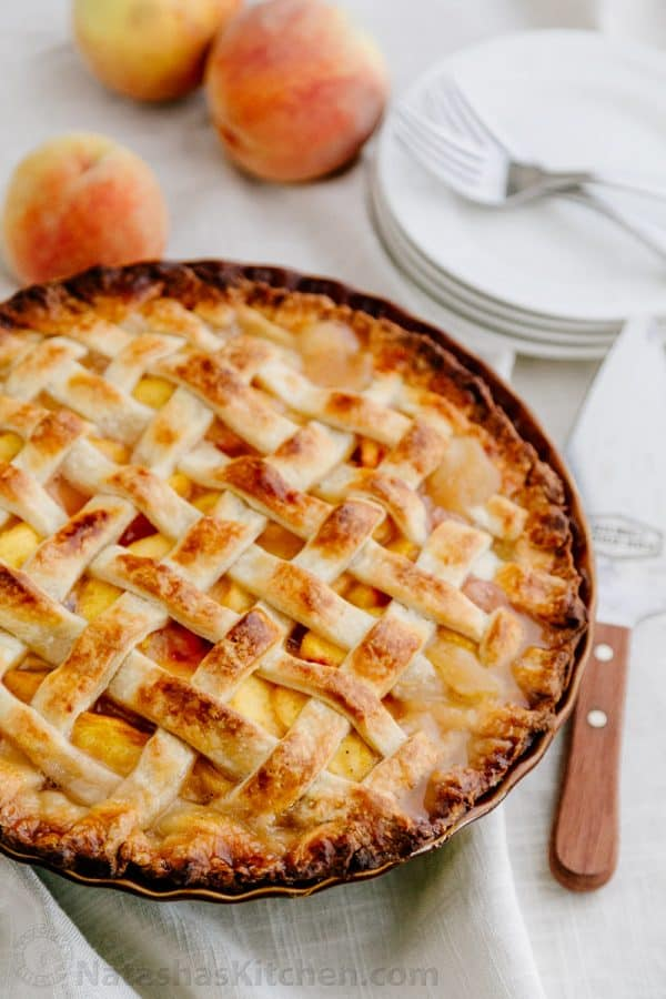 A peach pie with a spatula, plates, forks and fresh peaches beside it