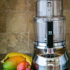 A Cuisinart food processor on a table with fruits around it