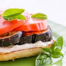 An open-faced eggplant and tomato sandwich garnished with basil on a green plate
