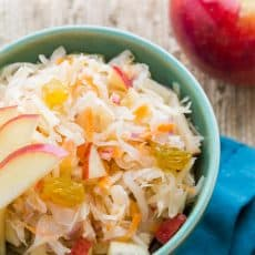 A green bowl of sauerkraut garnished with apples