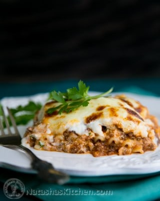 A plate with Lasagna with a fork besides it garnished with parsley