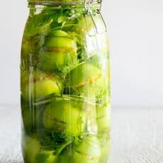 A clear glass jar with pickled stuffed green tomatoes