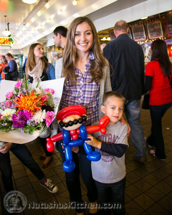 Natasha holding flowers and her son holding a ballon Mario at Pike Place Market