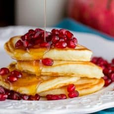 A plate of buttermilk pancakes and pomegranate seeds with syrup being poured on them