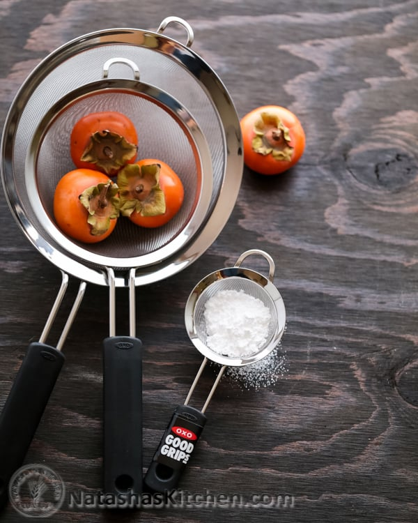Three OXO strainers on with powdered sugar and persimmons
