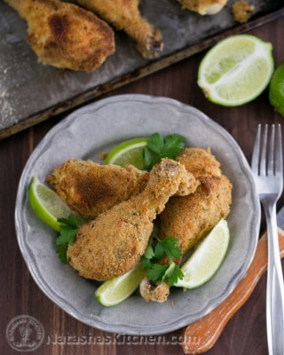 A plate of breaded baked chicken drumsticks garnished with lime wedges and cilantro