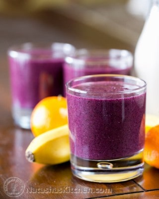 A close up of a glass cup with a blueberry smoothie with a banana and mandarines behind it