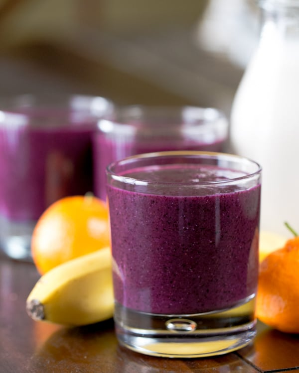 A close up of a glass of a purple smoothie with bananas and mandarins in the background