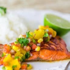 A plate of with teriyaki glazed salmon with peach salsa and rice and half a lime behind it