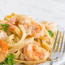 Creamy shrimp alfredo pasta on a plate with a fork beside it