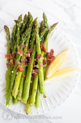 Roasted asparagus one a plate covered in bacon and lemon wedges on a plate