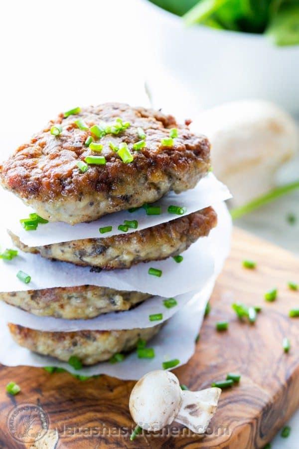 Chicken and mushroom patties stacked with parchment paper between each one garnished with chives