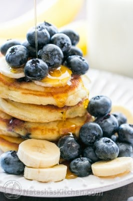 Stack of blueberry pancakes on a plate topped with syrup, blueberries, and sliced bananas.