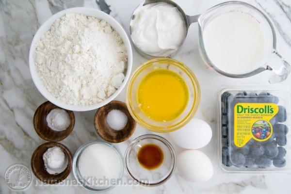 Pancake ingredients: flour, sugar, egg, milk, vanilla, salt, baking powder, baking soda, sour cream, blueberries in bowls/cups