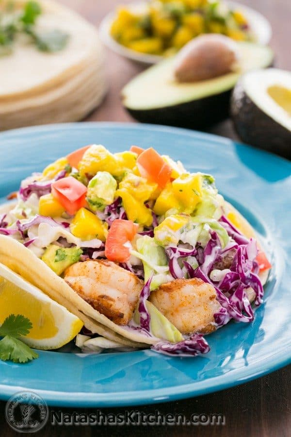 These Shrimp Tacos with Coconut Coleslaw & Mango Salsa are a yummy mouthful. Inspired by the famous fish tacos at Coconut's Fish Cafe in Maui.