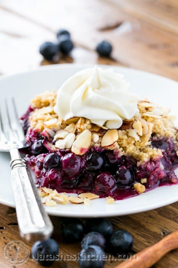 A plate and fork with a slice of blueberry crumble and whipped cream on it