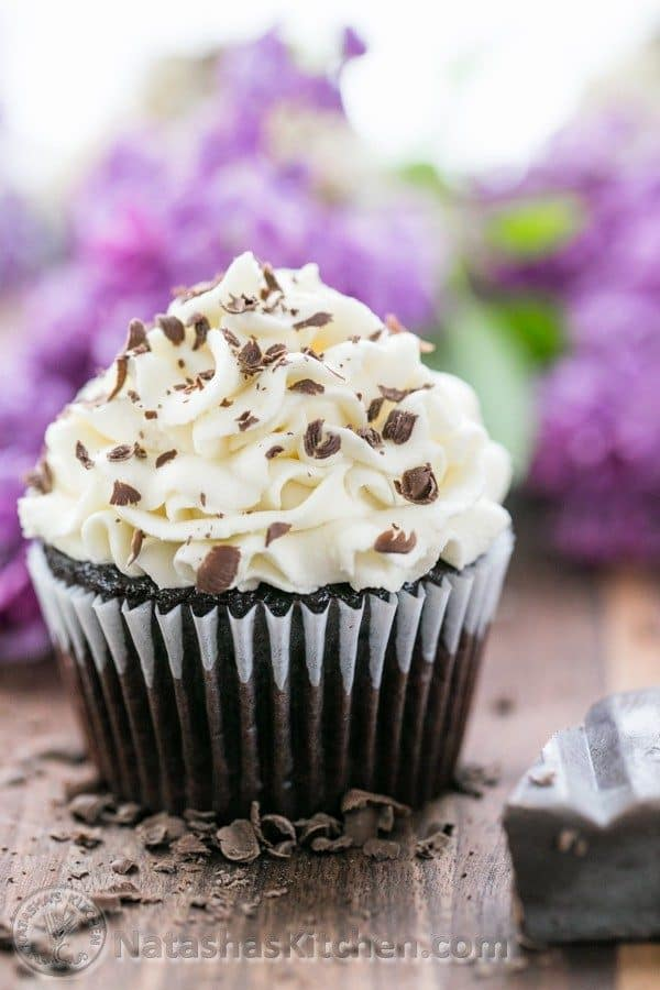 A close up of a dark chocolate cupcake with white chocolate frosting with flowers behind it