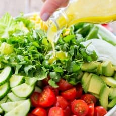 A bowl of Mexican salad with a lime dressing being poured over the salad